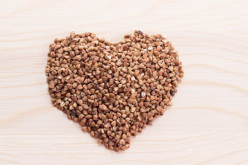 Heart-shaped buckwheat on wooden background