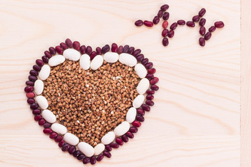 Heart-shaped buckwheat with beans on wooden background