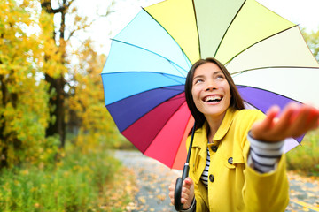 Autumn / fall woman happy in rain with umbrella