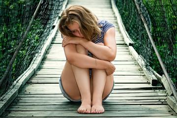 Портрет красивой грустной девушки на мосту