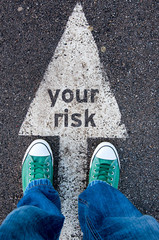 Green shoes standing on your risk sign