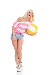 Laughing girl holding a beach ball