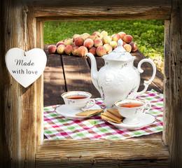 Tea set in garden in wooden frame with heart.
