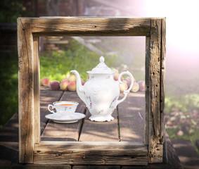 Vintage picture of tea set in garden in wooden frame.