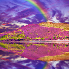 Colorful landscape scenery of rainbow over hill slope covered by