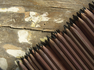 Row of identical pencils  on a old wooden background