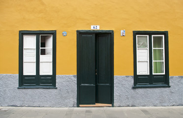 door and two windows on yellow wall