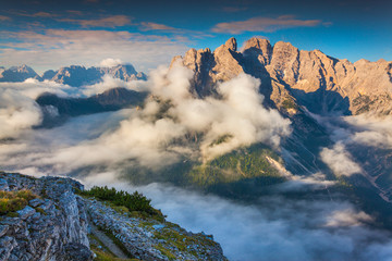Gruppo Del Cristallo mountain range at foggy summer morning. Dol