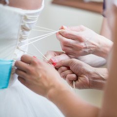 Bridesmaids helping the bride to put her dress on