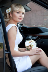 Portrait of a beautiful bride in car with bouquet of flowers.