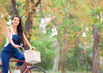 Teen girl on a bicycle in the park.