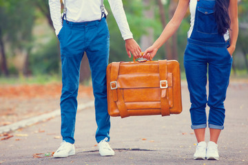 Couple holding suitcase in the park.