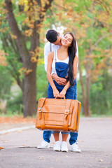 Teen couple with retro suitcase in the park in autumn time
