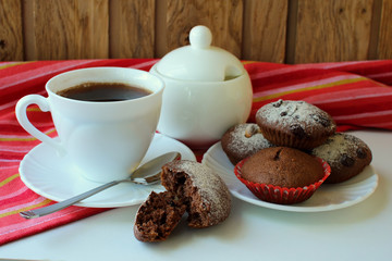A cup of brewed coffee and chocolate muffins.