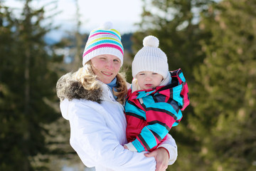 Mother and baby daughter hiking outdoors in winter