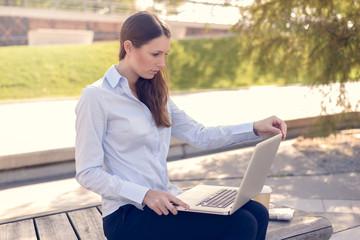 Junge Frau arbeitet draußen mit ihrem Laptop