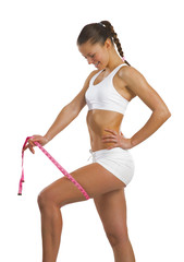 athletic woman measuring thigh