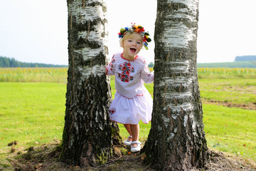 Little Ukrainian girl in traditional dress playing in the fields