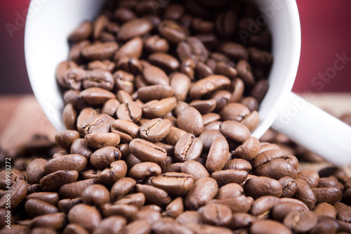 Fotobehang Koffiebonen Coffee beans falling out of white mug.