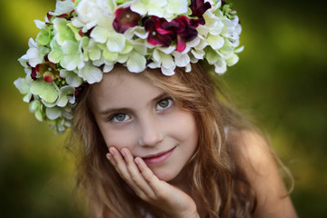 Beautiful smiling young girl in a wreath of flowers