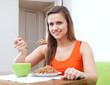 woman eats buckwheat porridge with spoon