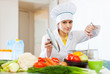 Cook looks into  saucepan in kitchen