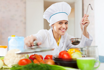 Happy  cook in white workwear works in  kitchen
