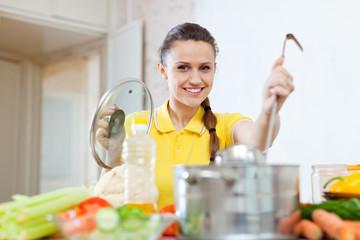 Portrait of  woman cooking  in saucepan