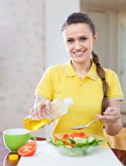 woman  pouring oil  into plate with veggie salad