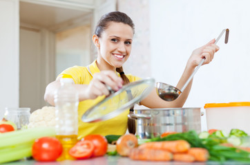 woman cooking  vegetarian food in saucepan