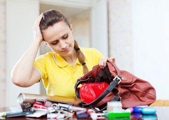inconsiderate woman lost something  in  purse