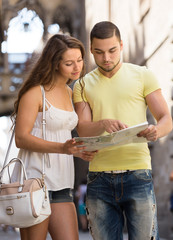 Two friends with map in the street