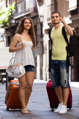 smiling young pair with luggage walking in city