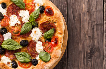 Pizza with salami and mozzarella top view with copy space rustic