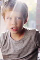Cute 6 years old boy sitting near the window