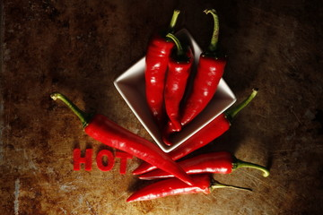 hot chili peppers with word hot in bowl on old vintage desk
