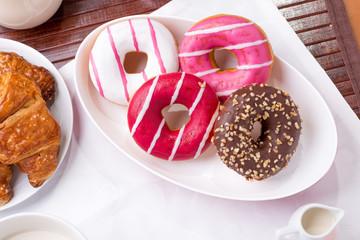 Prima colazione con donuts, brioches e  latte
