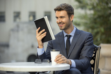 Businessman having coffee and using internet outside the office
