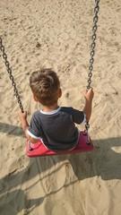Junge auf Schaukel am Strand