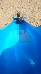 Junge auf blauer Rutsche am Strand