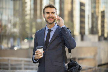 Businessman on the phone with office buildings in the background