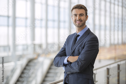 Portrait of happy businessman at an airport terminal - 69906615