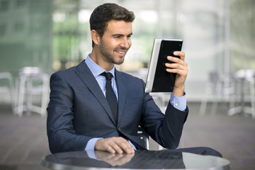 Happy businessman reading information from electronic device