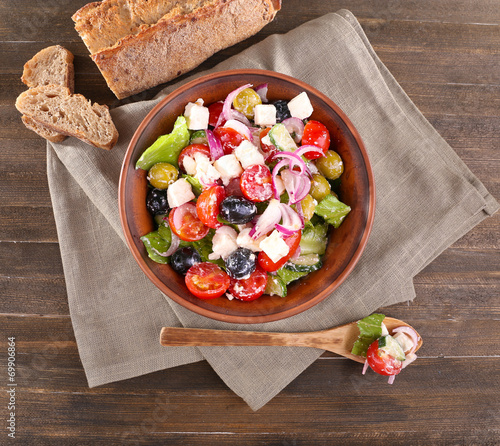 canvas print picture Greek salad served in brown bowl with bread