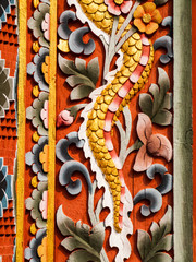 Bhutan traditional carved wooden decoration on red door