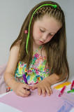 Pretty young girl drawing a picture with crayons - 69907215