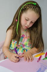 Pretty young girl drawing a picture with crayons
