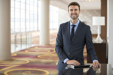 Portrait of young businessman with tablet in hotel lobby