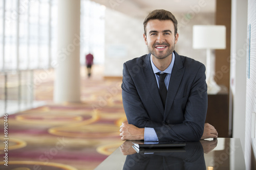 Portrait of happy young businessman waiting in hotel lobby