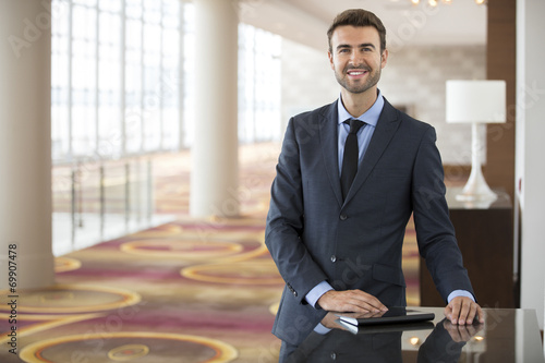 Portrait of young businessman with tablet in hotel lobby - 69907478